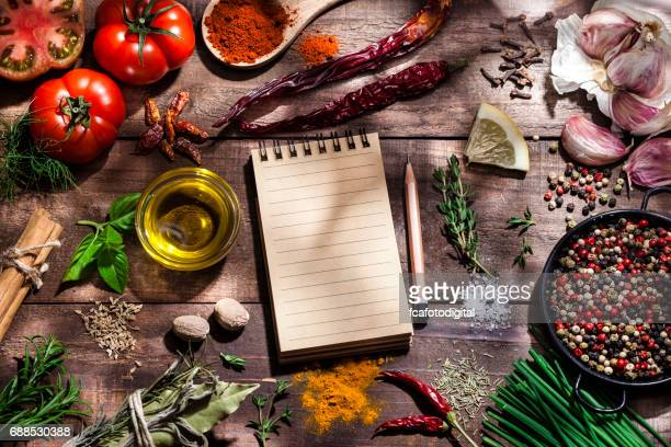 Blank cookbook with fresh ingredients for cooking and seasoning