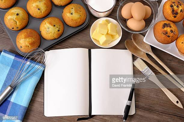 Blank cookbook with fresh muffins and ingredients