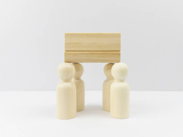 Blank cube shape wooden block toy on the top of standing wooden people for Leadership and Business design concept and activity. Development, Block Shape, Building - Activity. White colour background.