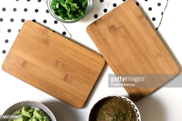 Blank cutting boards with fresh herbs and sauces around