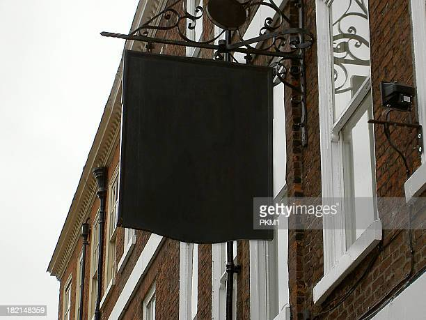 Blank English pub sign hanging from wall