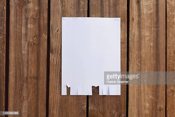 a blank flyer hanging on a wooden fence - flyer leaflet stock photos and pictures