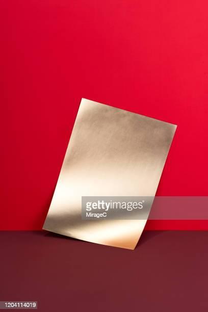 blank golden paper on red - stillleben stock-fotos und bilder