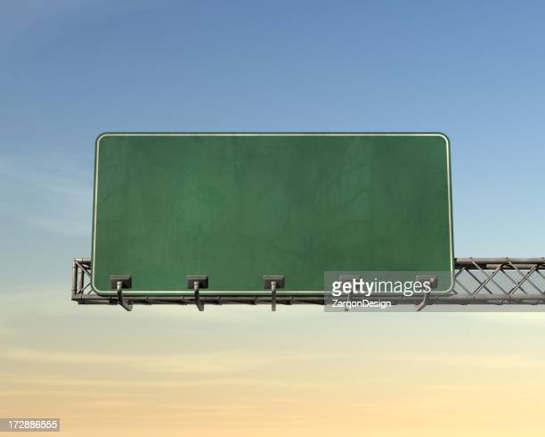 Blank green highway sign over blue and yellow sky