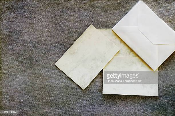 Blank gretting card and enveloppe for message. Flat lay composition, overhead and copy space. Subject captured againt soft window lighting over fabric and abstract background.