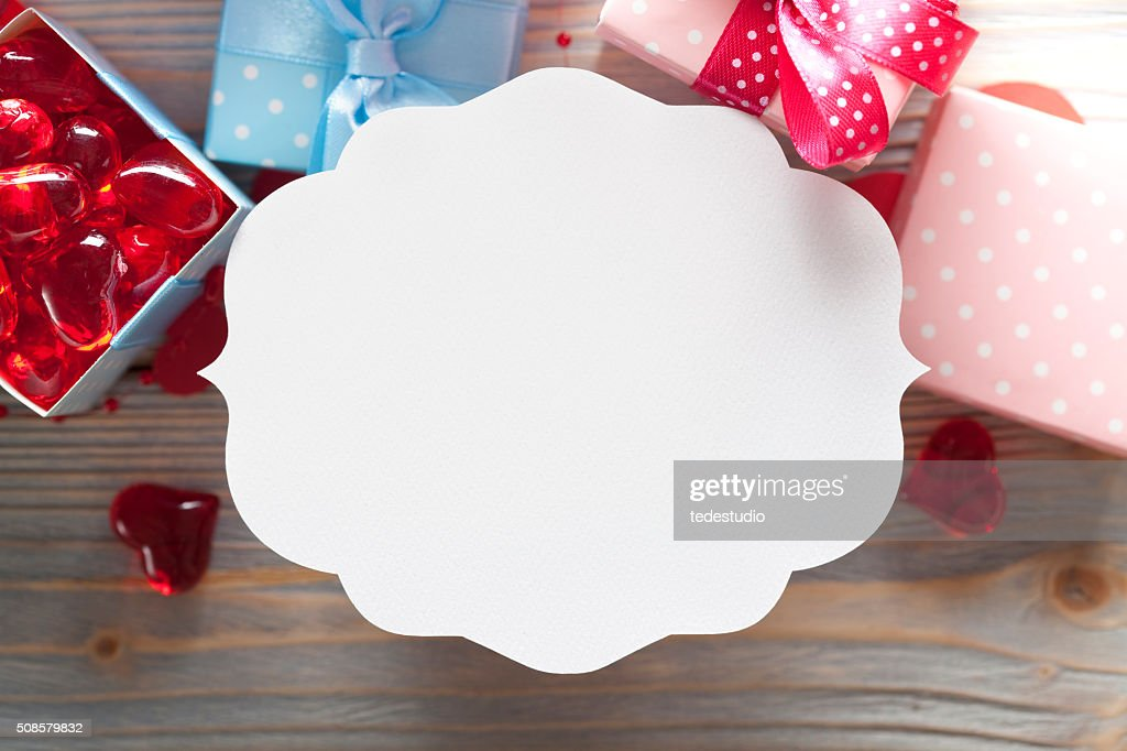 Blank label and gift boxes on wooden background : Stock Photo