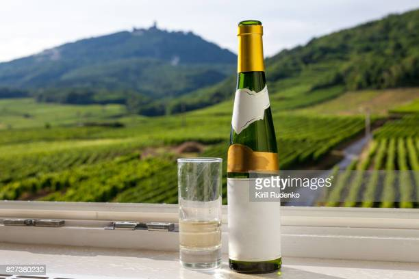 A blank labeled traditional Alsatian wine bottle and glass of white wine