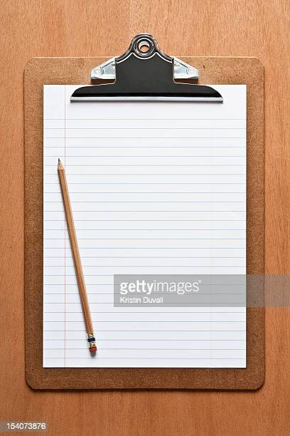 Blank lined paper with pencil, clipboard