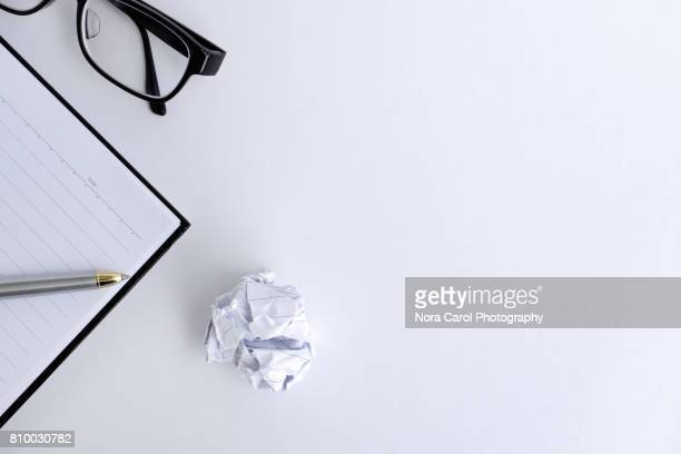 Blank note pad, eyeglasses, crumpled paper ball and pen