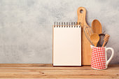 Blank notebook and kitchen utensils on wooden table over rustic background with copy space