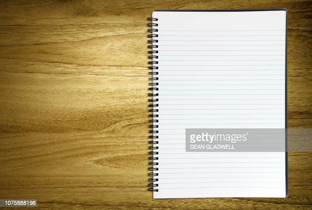 blank notebook on desk - schulbuch stock-fotos und bilder