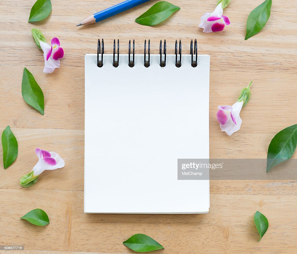 Blank notebook on wood background with flowers : Stockfoto