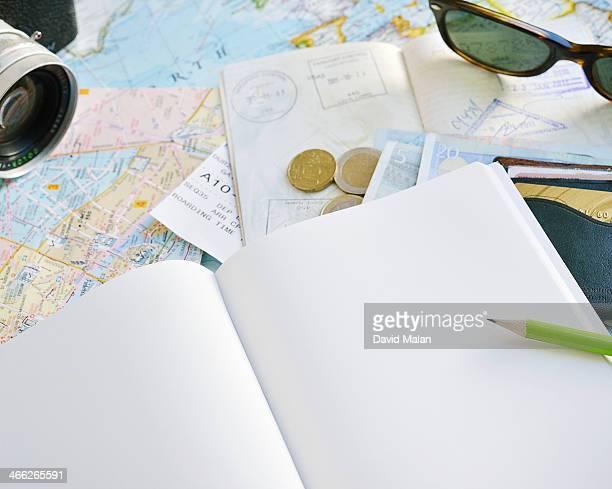 Blank notebook with maps, passport, money etc