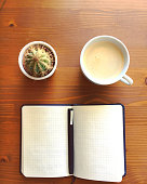 Blank notebook with pen, cactus and coffee on wooden table