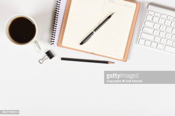 Blank notebook with pen, pencil, keyboard, coffee mug on white office table top view