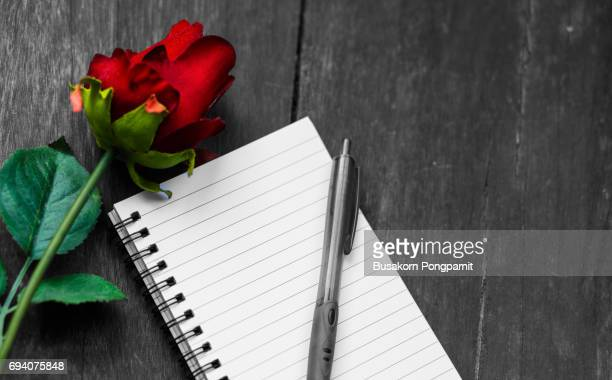 Blank notebook with rose on vintage wooden table