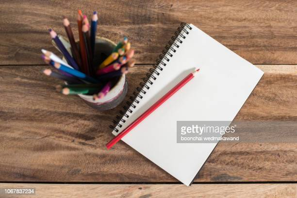 blank notepad and pencil color on wooden blackground - workbook stock photos and pictures