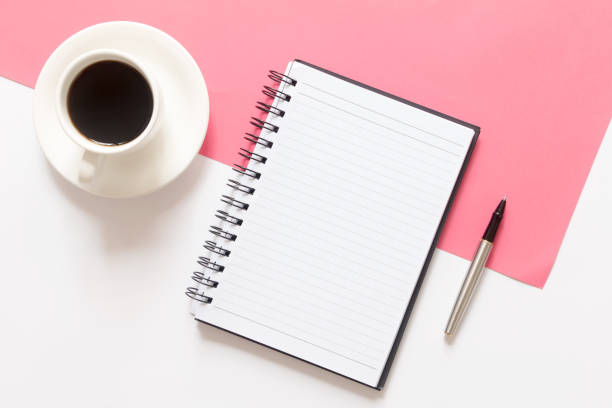 Blank notepad, coffee and pen on split color pink and white background