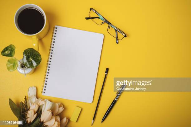 blank notepad page, coffee mug, pen and flower on yellow background. - agenda stock pictures, royalty-free photos & images