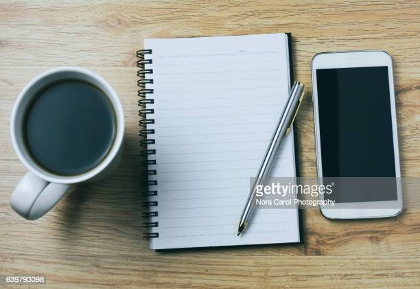 Blank notepad, pen coffee and smartphone