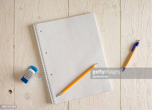 Blank notepad with pencils and eraser on table