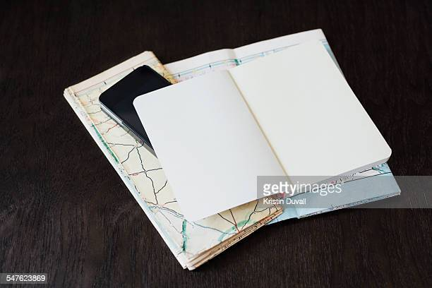 Blank open journal with phone and vintage maps