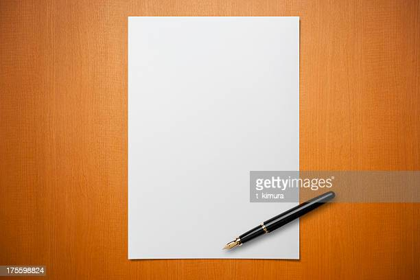 blank paper on desk with a pen - bericht stockfoto's en -beelden