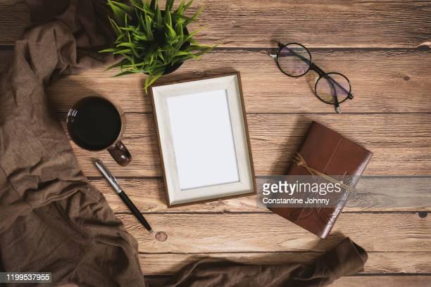 blank picture frame on rustic wood - tischflächen aufnahme stock-fotos und bilder