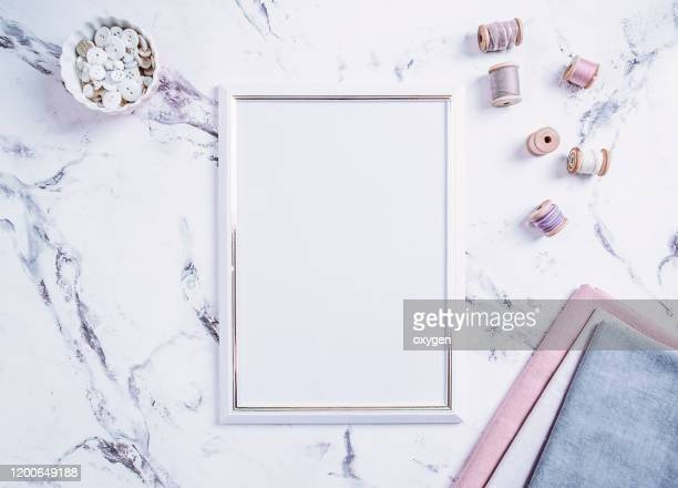 blank picture frame sewing spool threads and tools for needlework of threads on pink, gray color over marble table background. mockup. flat lay, top view. free blank place for text - ribbon sewing item stock pictures, royalty-free photos & images
