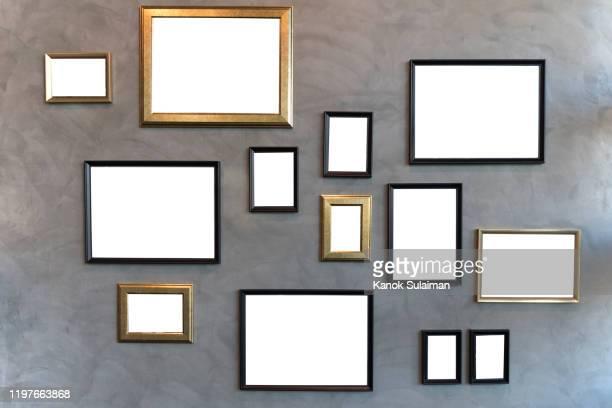 blank picture frames hanging on cement wall - fotografi bild bildbanksfoton och bilder