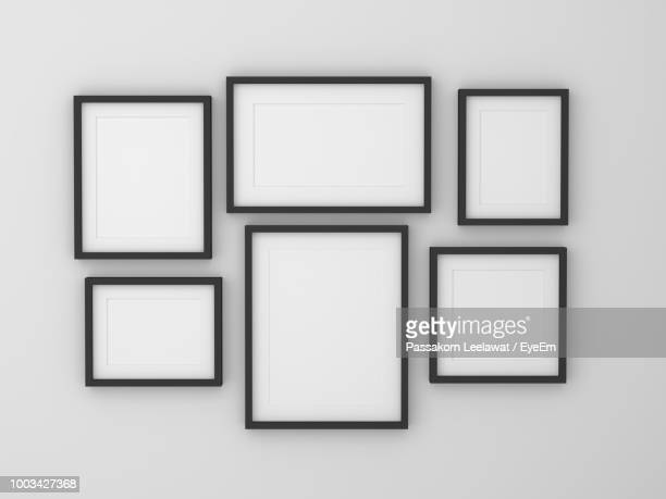 blank picture frames hanging on white wall - muur stockfoto's en -beelden