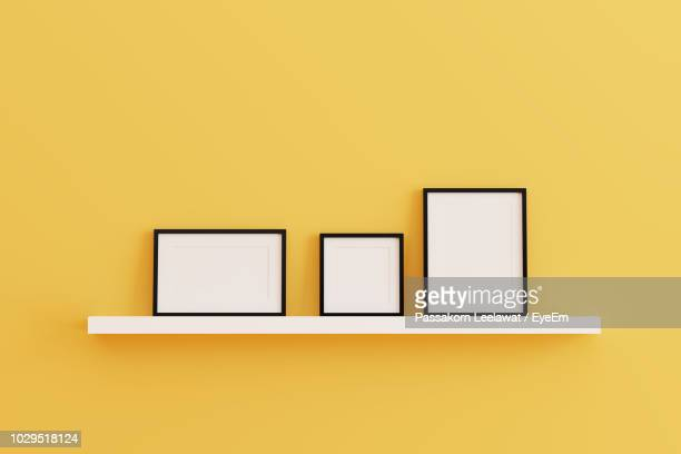 blank picture frames on rack against yellow wall - photography stock pictures, royalty-free photos & images