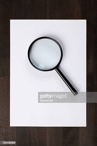 a blank piece of paper and a magnifying glass - magnifying glass stock pictures, royalty-free photos & images