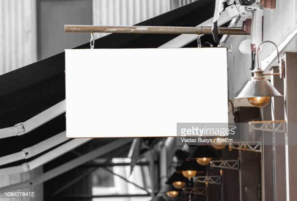 blank placard by lighting equipment - hanging sign stock pictures, royalty-free photos & images