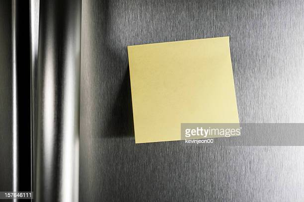 A blank post it note on a stainless steel refrigerator door