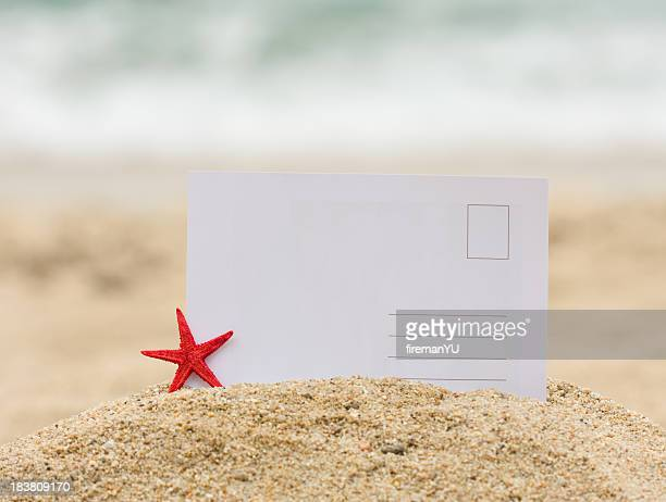 Blank postcard stuck in mound of sand next to a starfish