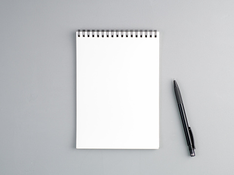 blank sheet of notebook with a spiral and pen on a neutral gray textured  background 942930688