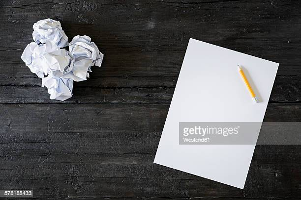 Blank sheet of paper, pencil and crumpled papers on black wood