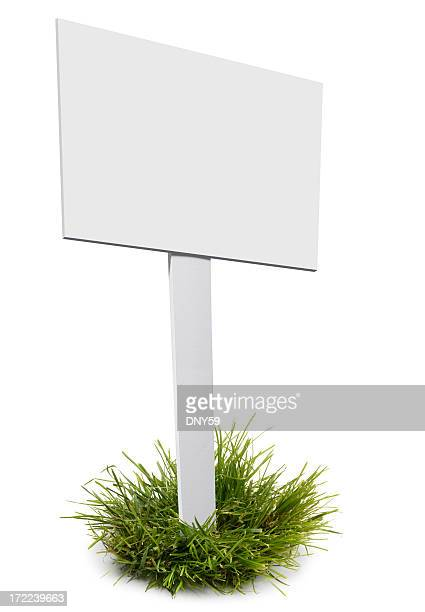 Blank sign and post stuck in to tuft of grass