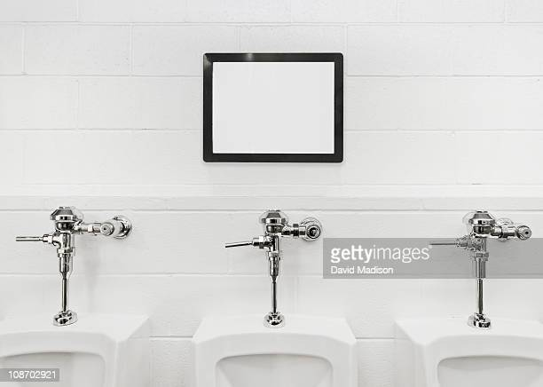 Blank sign board above urinals.