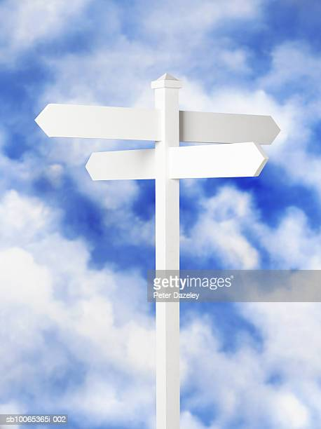 Blank sign post against cloudy sky