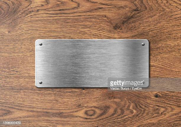 blank silver plate on wooden doors to add text, name or logo - nameplate stock pictures, royalty-free photos & images