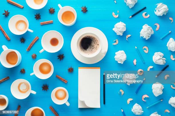 blank sketchbook with a minimalist pattern of empty coffee cups, crumpled paper balls and pencil shavings on a colorful blue background. creative profession workplace concept. - food journal stock-fotos und bilder