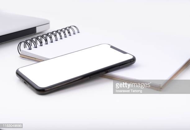 blank smartphone with white blank screen is put over a laptop. - iphone mockup stock pictures, royalty-free photos & images