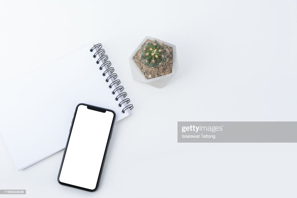Blank smartphone with white blank screen is put over a laptop. : Stock Photo