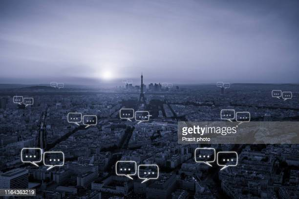blank space for text on paris city and bubble chat for communication. communication chat icon above cityscape on blue tone concept. - big tech foto e immagini stock