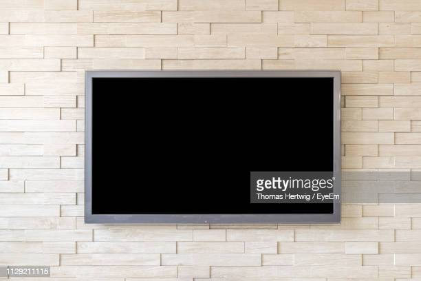 blank television screen on wall at home - televisión fotografías e imágenes de stock
