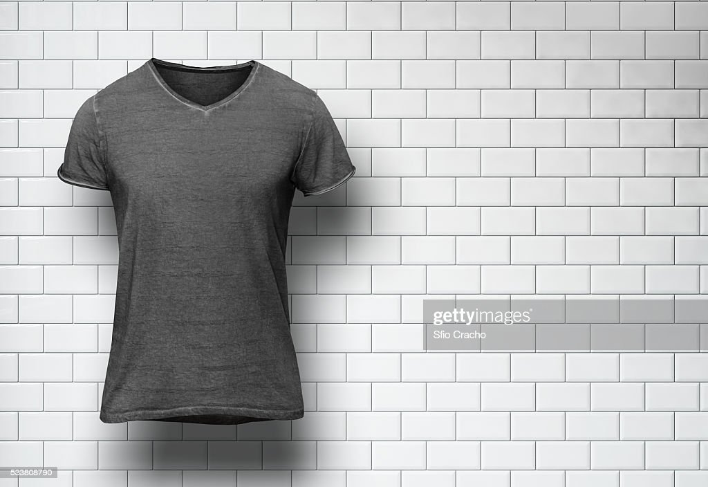 Blank t-shirt on white tile wall background : Foto stock