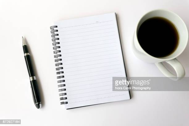 blank white diary with pen and coffee on white background - stift stock-fotos und bilder
