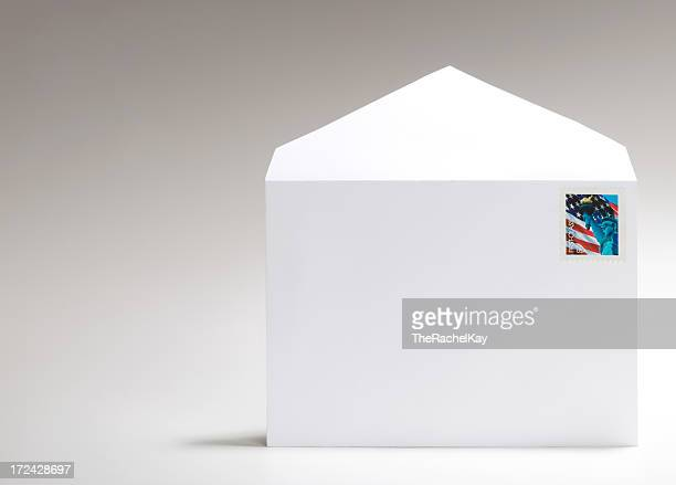 Blank, white envelope with American flag stamp on white